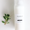 100 ml cleanser in white airless pump next to a plant clipping