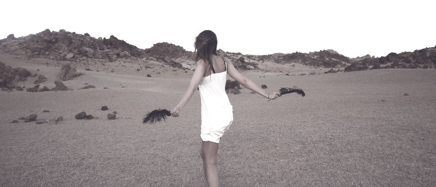 girl baring skin white dress in sand dunes with young skin type