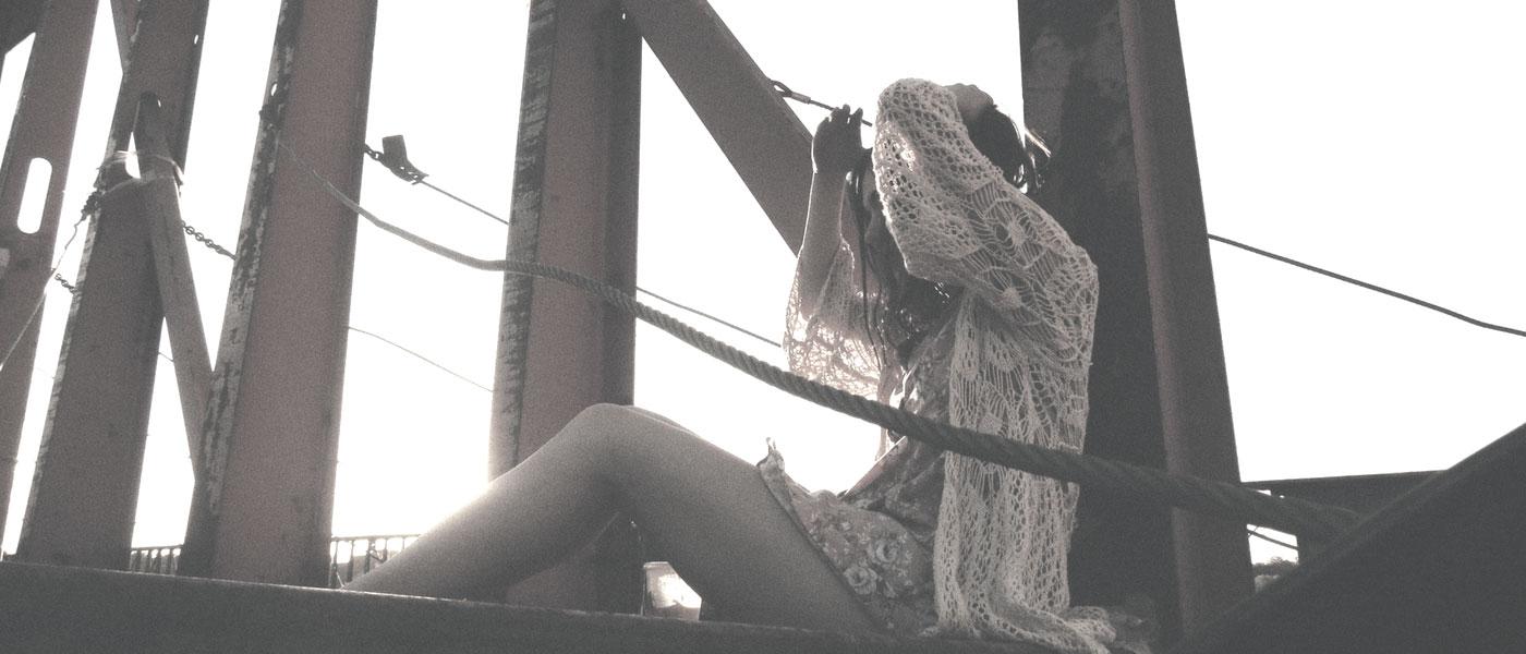 girl sitting on bridge exposing skin type to the sun