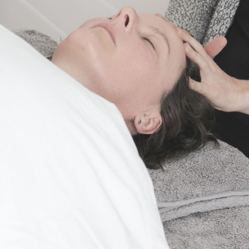 client on bed having natural face lift massage massage